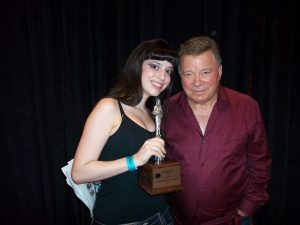 "Deena Roth, RunnerUp at the 1st Annual Dragon Con Miss Star Trek Universe Pageant in 2010, here with William ""Captain James T. Kirk"" Shatner and her trophy which he signed at a subsequent 2011 Star Trek Convention in Nashville."