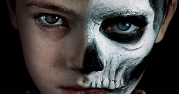 Close up of child with half his face painted as a skull for the move The Prodigy