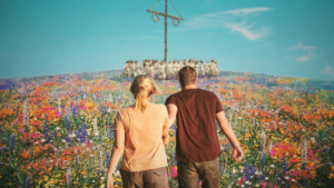 A man and woman walking througha field of flowers towards a group dancing around a maypole in Midsommar