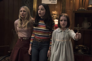Three girls fighting demons with the Annabelle doll in the bachground