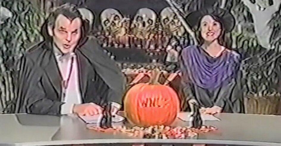 News anchors dressed in Halloween costumes on set with pumpkin