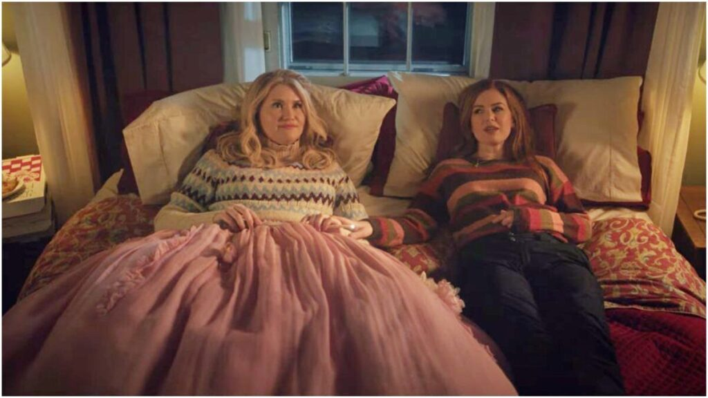 Jillian Bell and Isla Fisher relax on a bed in the film GODMOTHERED on Disney+